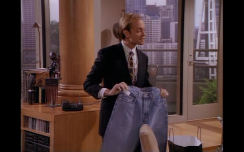 David Hyde Pierce as Niles Crane holds up a pair of blue jeans.