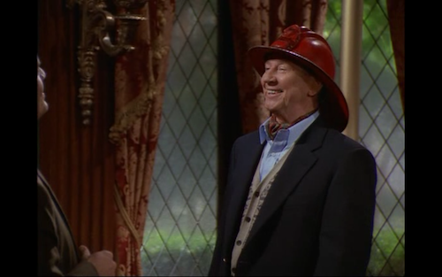 Donald O'Connor wearing a red fireperson's hat.