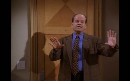 Frasier holds up two hands to convince people to do something.