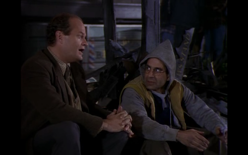 Frasier and Manu sit in front of Manu's burned newspaper stand.