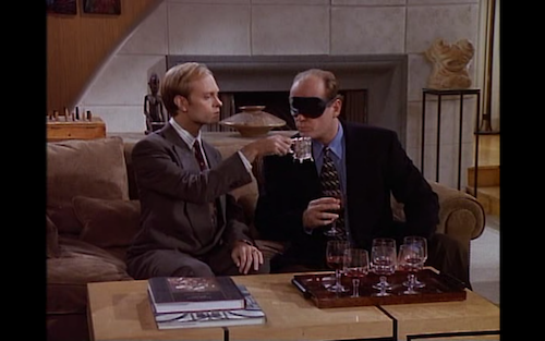 Niles holds a silver spittoon for a blindfolded Frasier to spit his wine into during a tasting practice.
